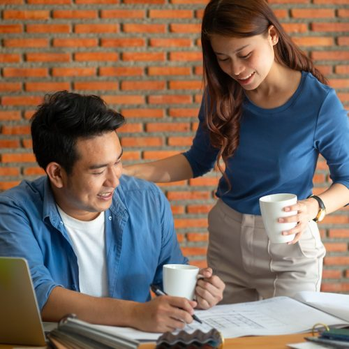 Asian architecture or engineer discussing with his partner in office with laptop, lifestyle concept.  Brick wall background.