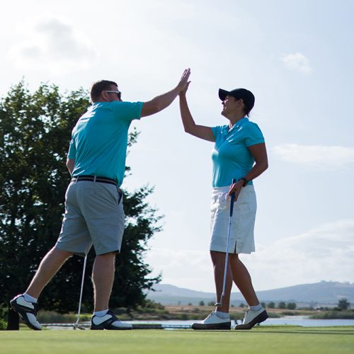 Two golfers enjoying a game of golf give each other a high five after a great shot. Mid adult couple playing golf.